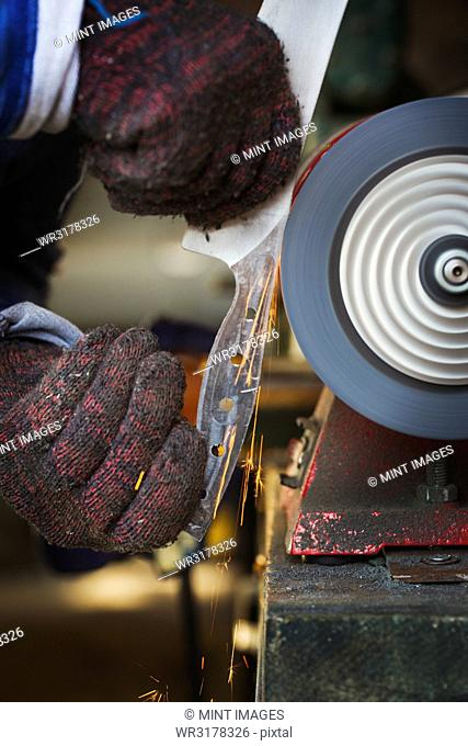 Close up of man in workshop holding a newly cut knife blade, smoothing the surface with a rotating surface grinder