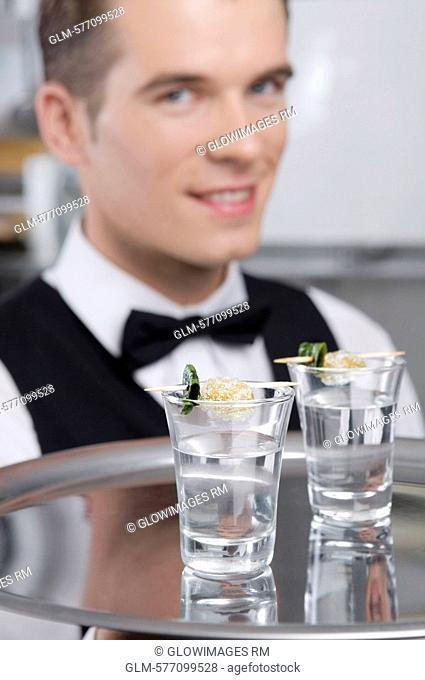 Waiter holding a tray of tequila shots
