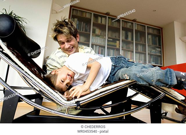 Son lying on a chaise longue with his father sitting beside him