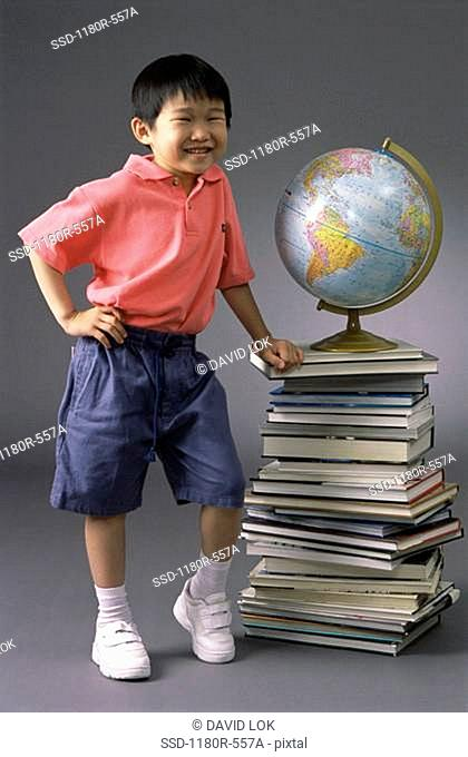 Portrait of a boy standing next to a pile of books and a globe