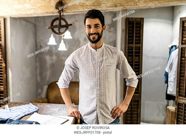 Portrait of smiling man wearing shirt in menswear shop