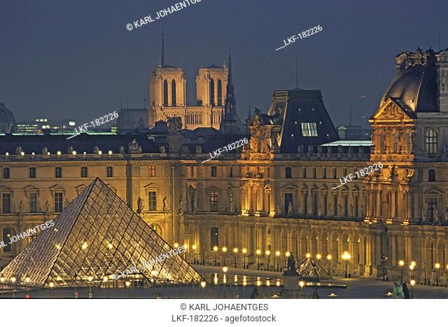 Louvre Museum with IM Pei Pyramide and Notre Dame in background, illumated at night, Paris, France