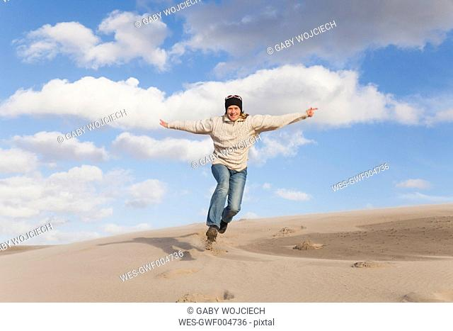 Enthusiastic mature woman running and jumping on sand dune