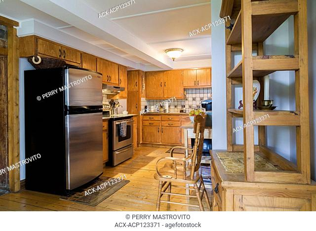 Kitchen with cherrywood cabinets, wooden buffet and pinewood floorboards inside an old circa 1752 Canadiana style fieldstone house, Quebec, Canada