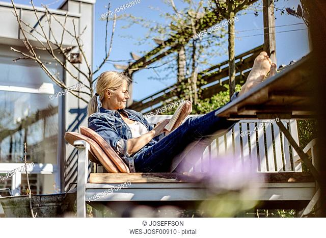 Smiling woman reading book on garden bench