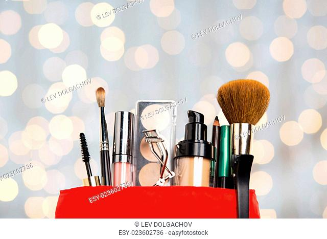cosmetics, makeup, holidays and beauty concept - close up of cosmetic bag with makeup stuff over lights background