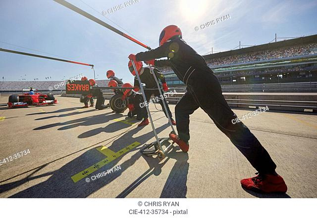 Pit crew preparing for formula one race car pit stop in pit lane