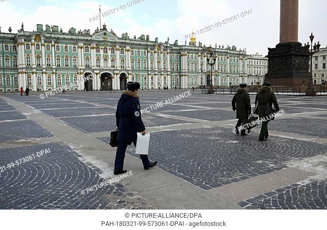 15 March 2018, Russia, St. Petersburg: Passers-by walking across the Palace Square before the Hermitage with the Winter Palace and the AlexanderColumn in...