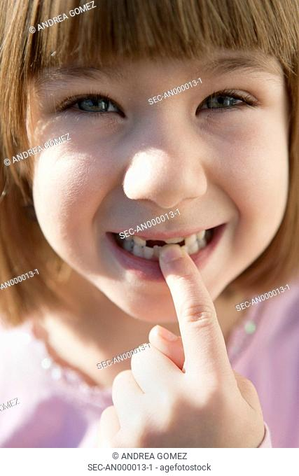 Portrait of girl (4-5) pointing her missing teeth