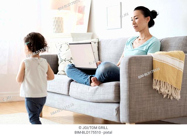 Mother using laptop ignoring baby daughter