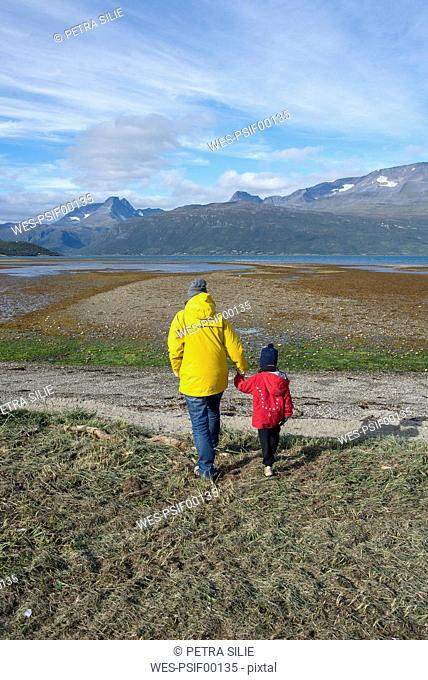 Norway, mother and daughter walking to the Lyngen fjord