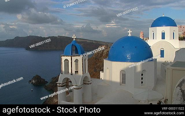 oia (ia), Santorini, Cyclades Islands, Greece : zoom back to see Blue dome of a Greek Orthodox church looking down at the sea