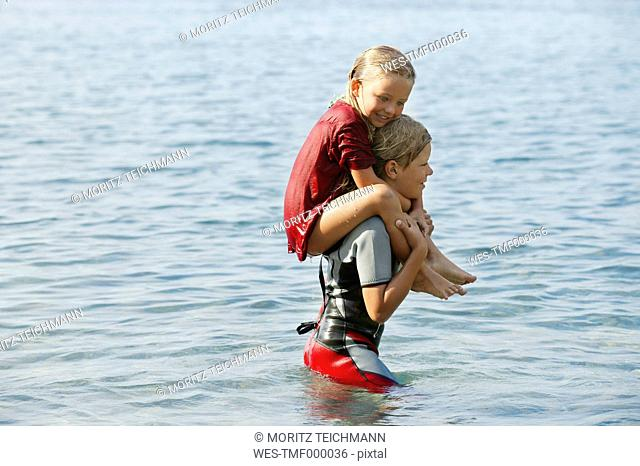 Spain, Mallorca, boy carring little sister on his shoulders in the sea