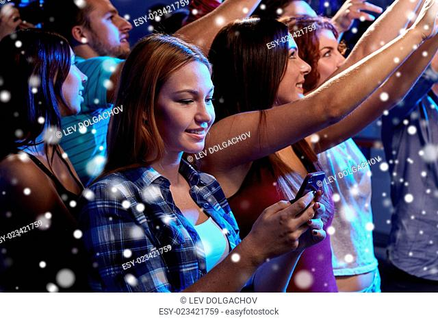 party, holidays, celebration, nightlife and people concept - smiling young woman with smartphone texting message at concert in club and snow effect
