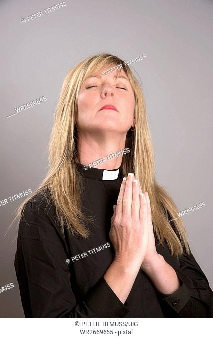 Portrait of a Female Clergy Wearing A Black Shirt And Dog Collar Praying