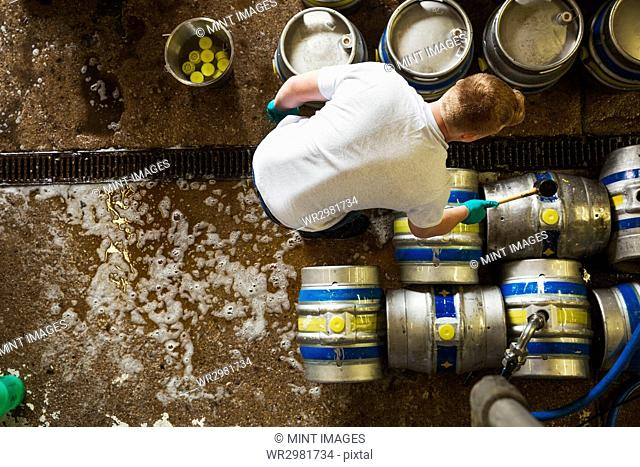 Directly above view of a man working in a brewery, metal beer kegs standing on the floor