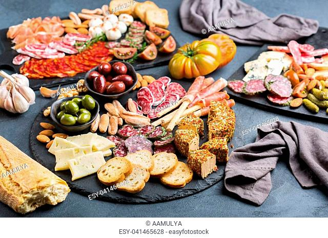 Still life, food and drink, holidays concept. Assortment of spanish tapas or italian antipasti with meat, ham, olives, cheese, nuts and bread on a black table