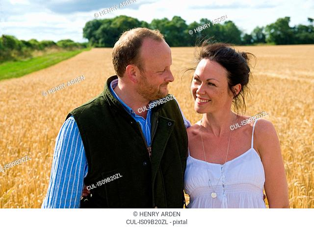 Mid adult couple walking through field, smiling