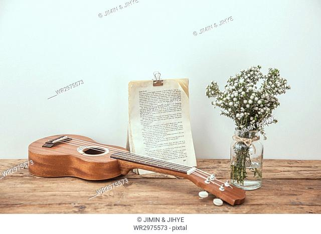 Ukulele, flowers in glass jar and clipped book