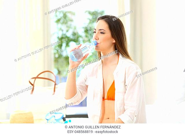 Woman drinking water from a bottle in an hotel room in summer vacations