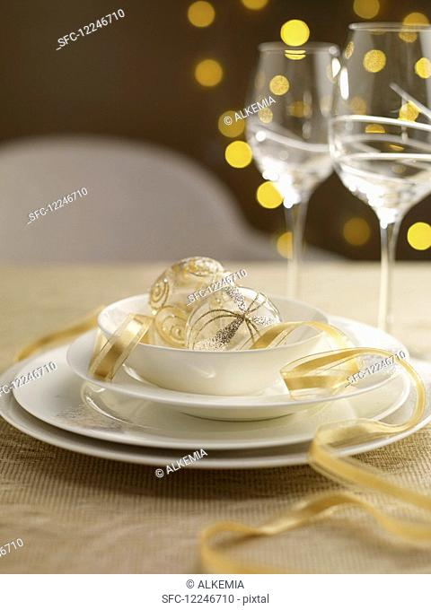 A Christmas table setting with gold ribbon and baubles