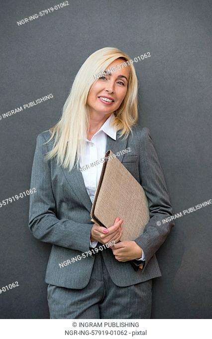 Image of pretty businesswoman standing near wall holding folder and looking away