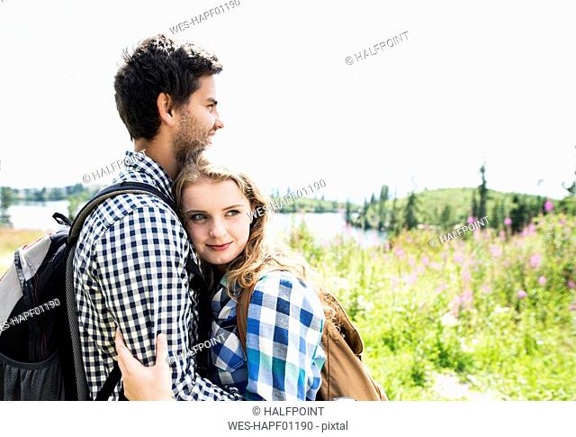 Young couple embracing on a hiking tour