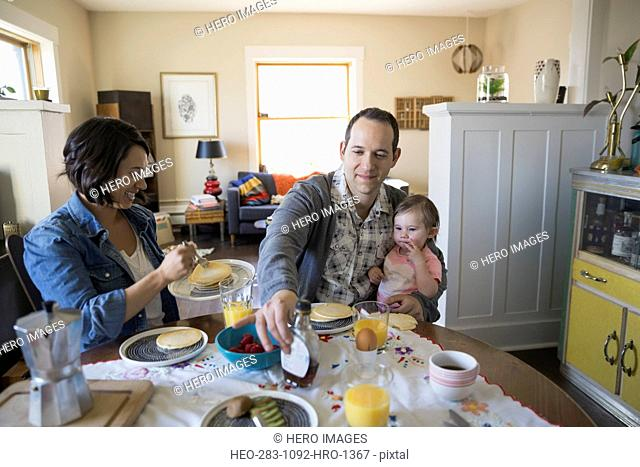 Young family enjoying breakfast at dining table