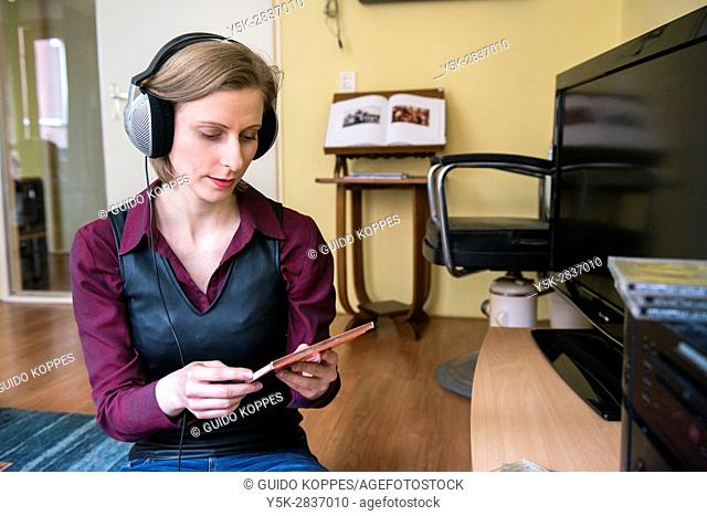 Tilburg, Netherlands. Young adult caucasian woman enjoying music from her stereo hifi set using a headset and a cd or compact disc