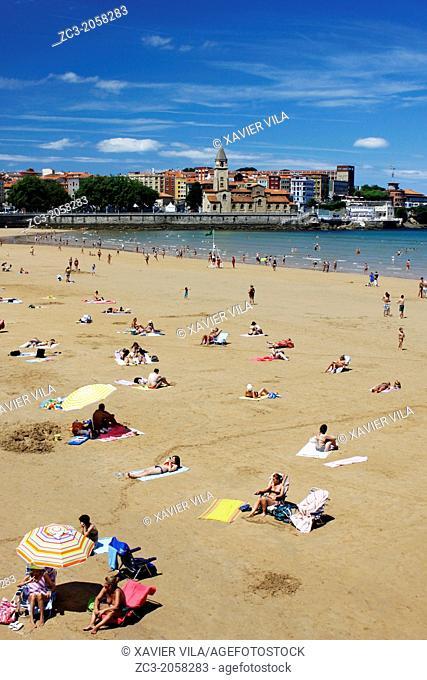 Beach of San Lorenzo with umbrellas and San Pedro Church, city of Gijon, Asturias, Spain