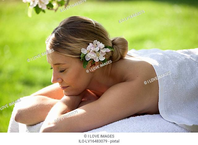 A young woman laying on a massage table under a tree in blossom, eyes closed