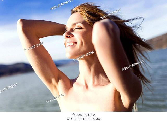 Happy young woman in front of lake enjoying sunlight