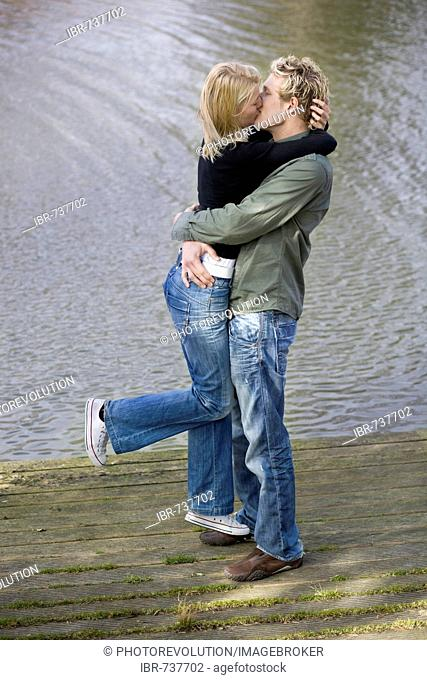 Man lifting woman on a wooden dock, kissing