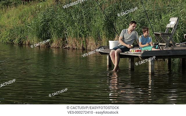 Father and son enjoying fishing together on lake