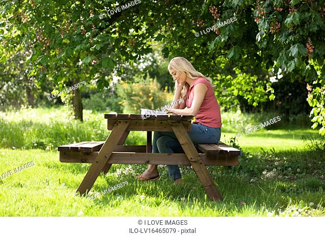A young woman sitting on a garden bench reading a book