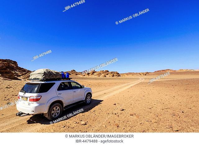Off road vehicle in rock desert, Damaraland, Kunene Region, Namibia