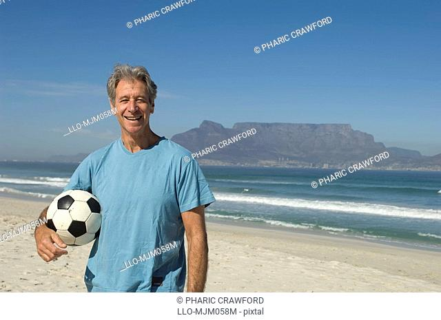 Senior man holding soccer ball under arm on beach, Table Mountain in background, Table View, Cape Town, Western Cape Province, South Africa