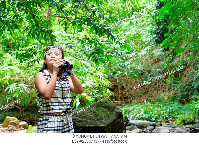 Beautiful young girl hiking is using binoculars look for birds in tropical forest near the waterfalls in Thailand