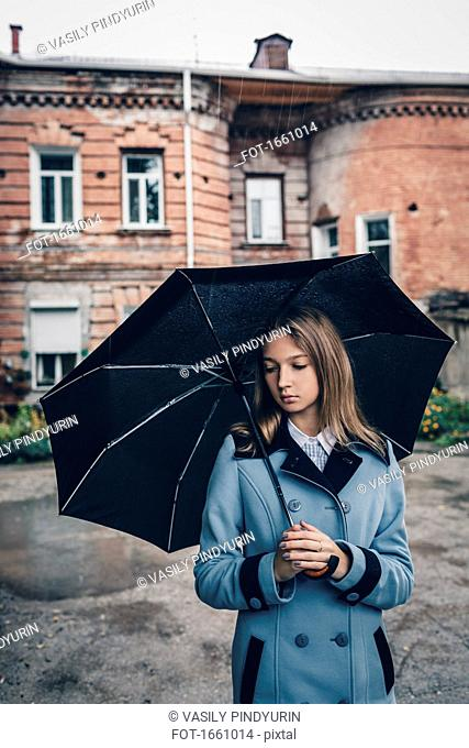 Thoughtful teenage girl holding umbrella standing against building
