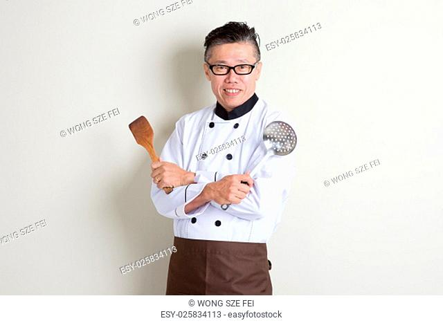 Portrait of confident 50s mature Asian male chef in uniform hands holding kitchen tools, standing on plain background with shadow, copy space