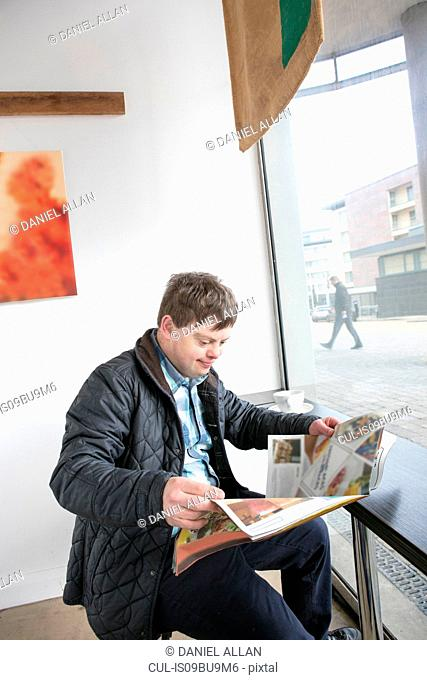 Man with down syndrome reading newspaper by cafe window