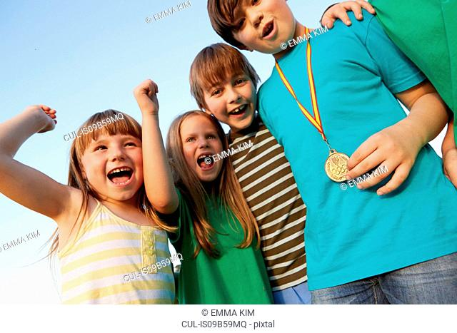 Boy with gold medal and team cheering against blue sky