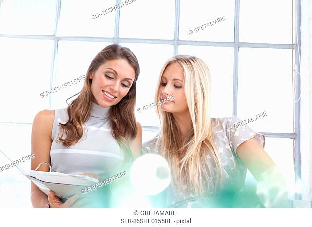 Businesswomen reading binder together