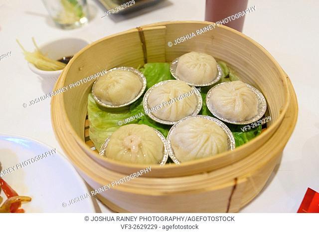 Chinese food pork dumplings in a steamer basket at an Asian Restaurant