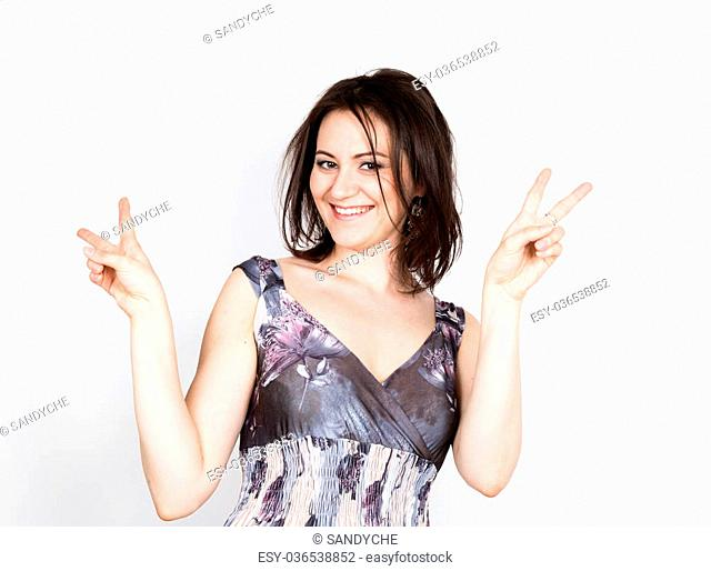 beautiful young brunette woman in a colorful dress posing and expresses different emotions. woman's hands shows various signs, disco. close-up portret