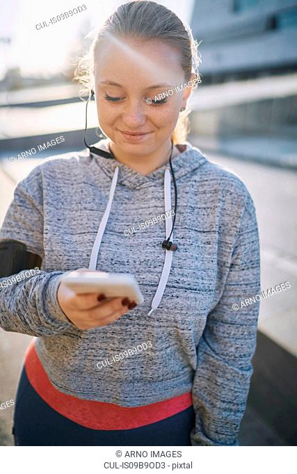 Curvaceous young woman training, looking at smartphone
