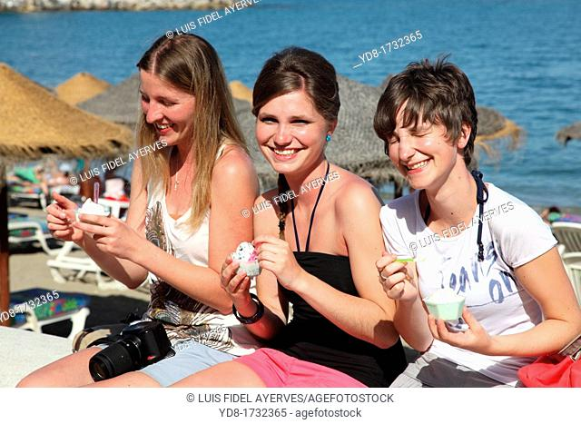 Young women eating ice cream on the promenade of Fuengirola, Malaga, Andalucia, Spain