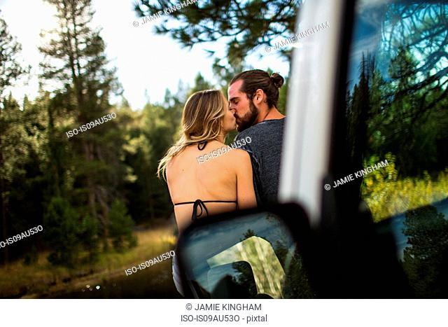 Rear view of romantic young couple kissing at riverside, Lake Tahoe, Nevada, USA
