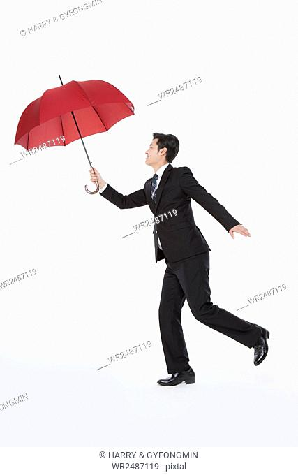 Side view of business man with a red umbrella standing on one foot