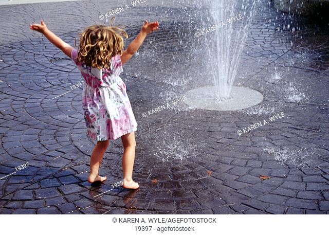 Barefoot little girl with curly hair, in dress, arms wide, enjoying spray from street-level fountain
